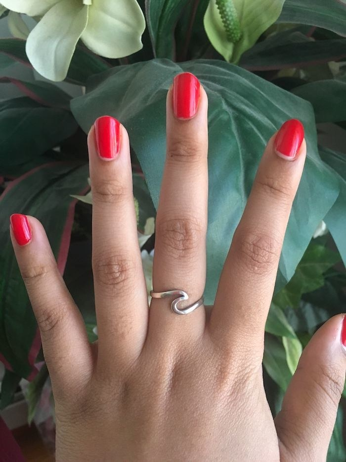 BuzzFeed writer Jasmin Suknanan's hand wearing the wave ring. It's silver and the metal is bent in the shape of a single wave.