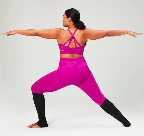 Model wears a pink Core 10 'Icon Series' The Ballerina Sports Bra with a criss-cross design on the back