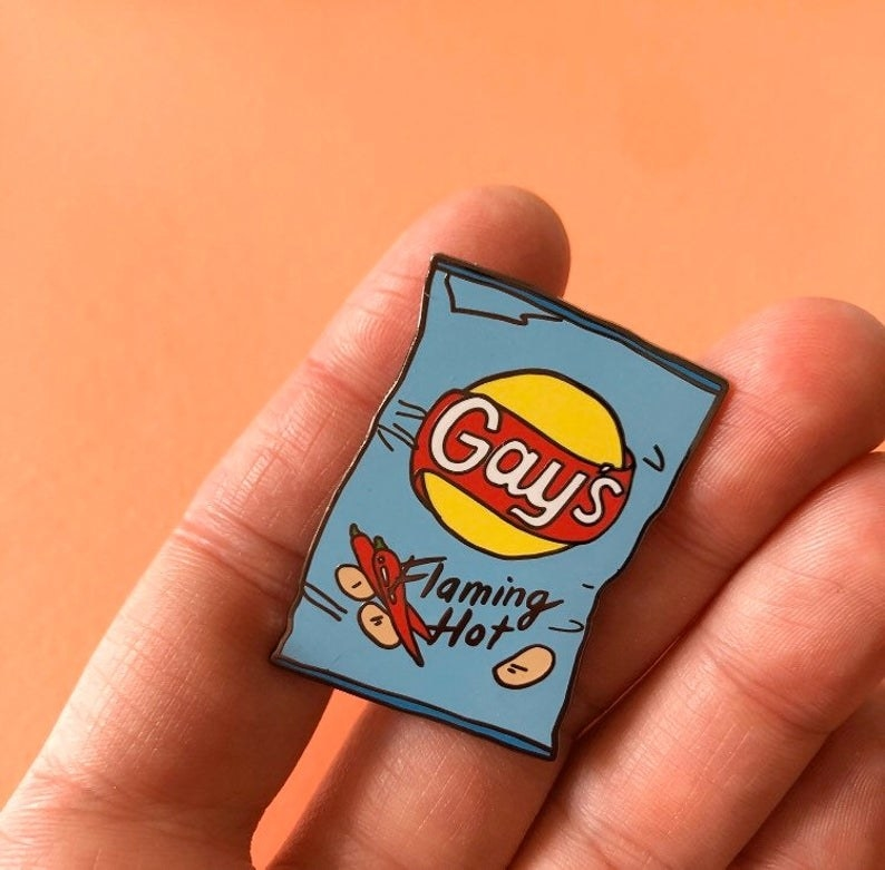 """Hand holding the """"gays flaming hot"""" chip bag pin"""