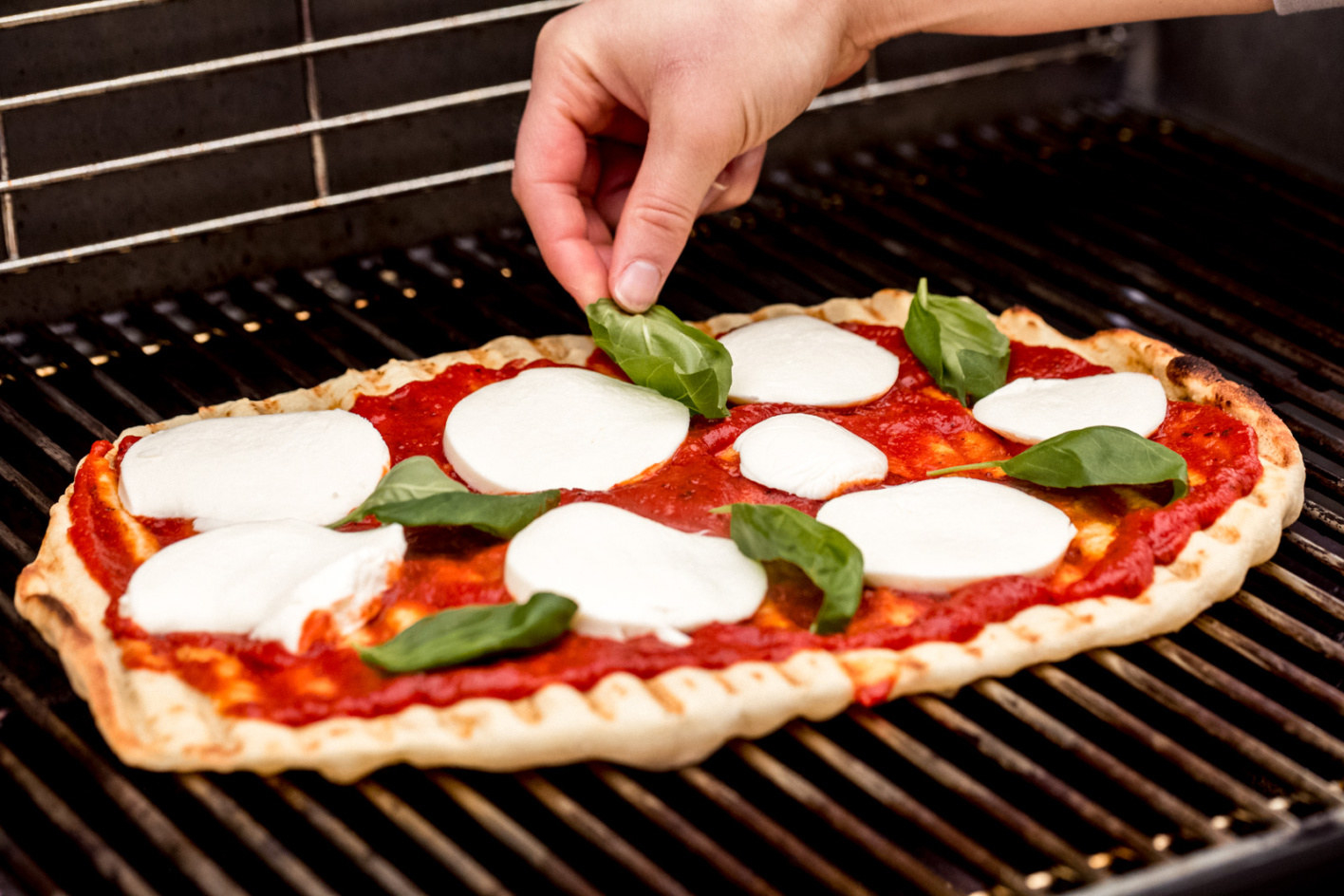 A margarita pizza topped with tomato sauce, mozzarella, and fresh basil on a grill.