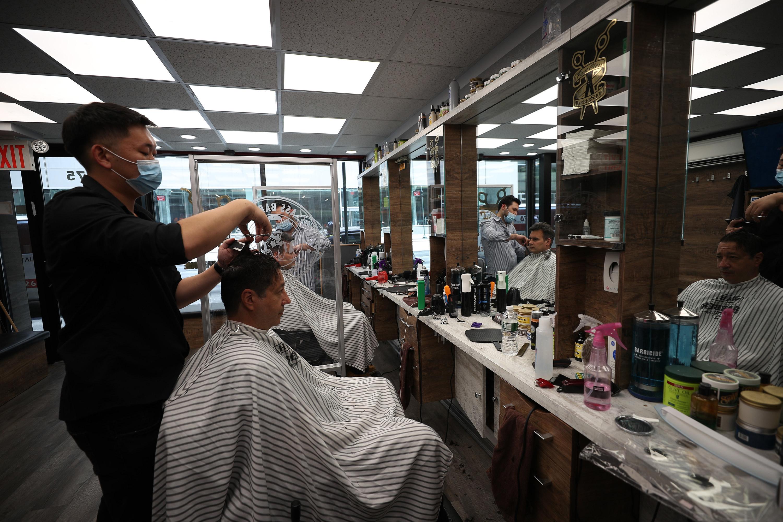 Barber cuts customer's hair