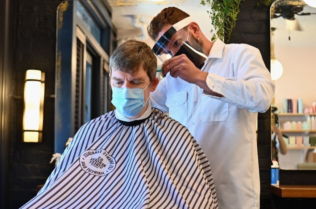 Barber wears PPE as he cuts a client's hair