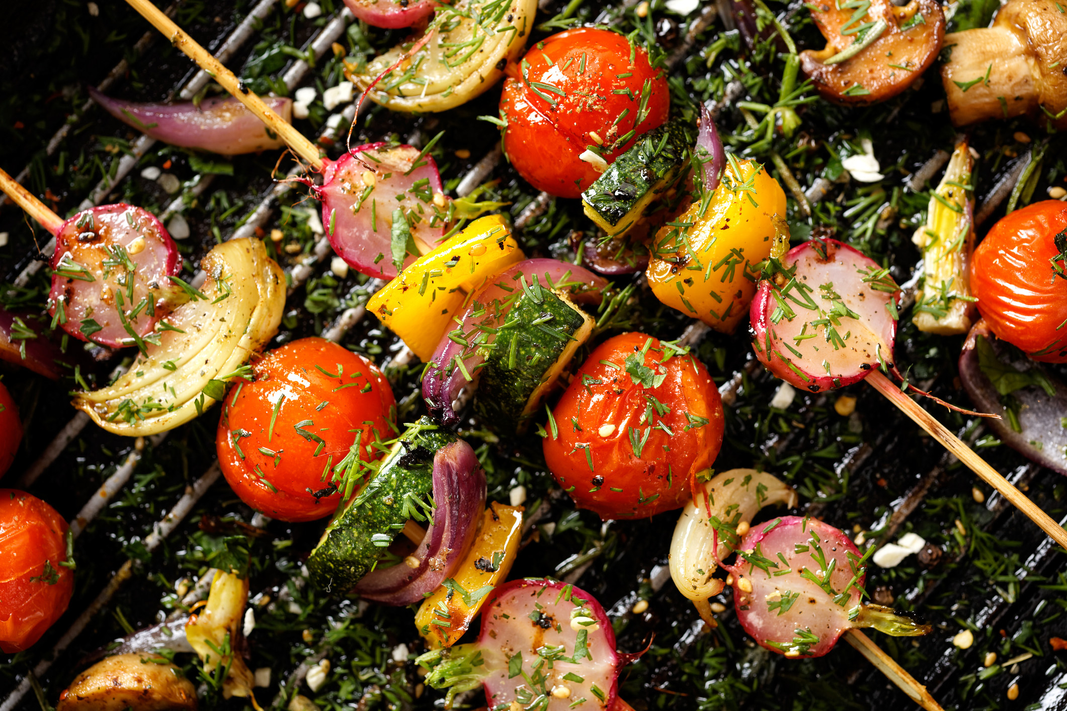 Vegetable skewers with tomato, onion, zucchini, and pepper on the grill.