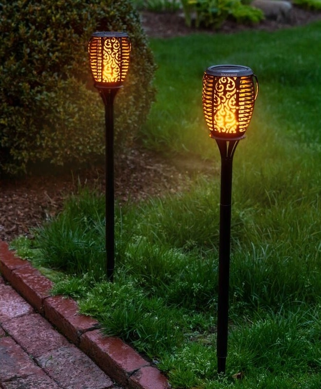 The carving-style torches sticking out of grass