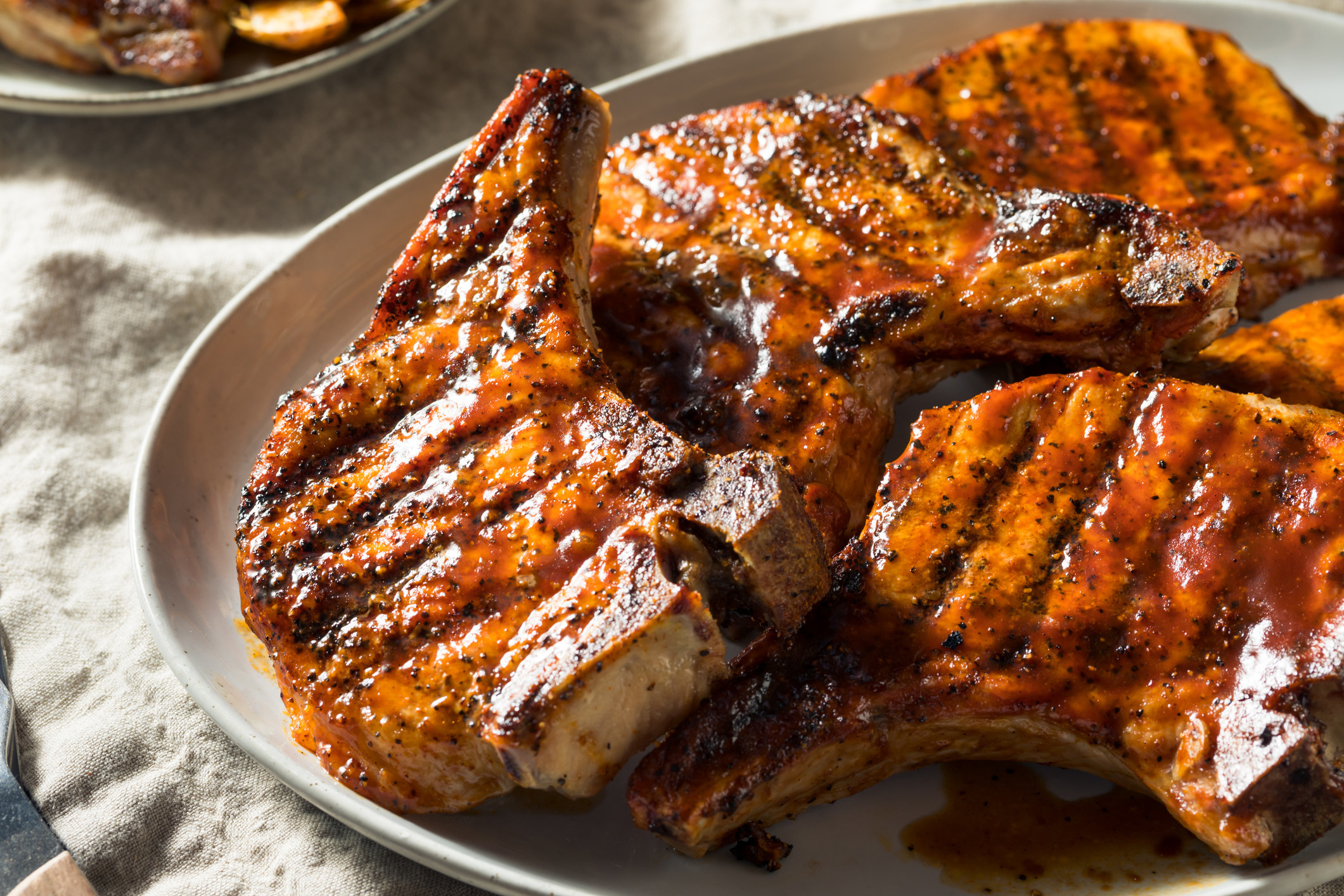 A plate of grilled bone-in pork chops with barbecue sauce.
