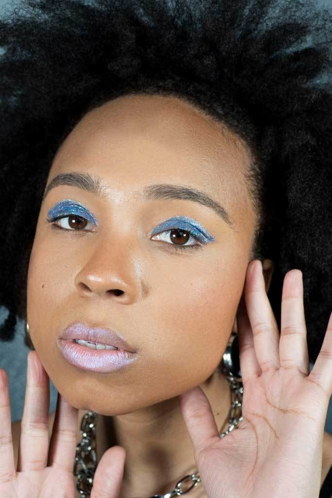 Model wearing blue glitter liner as eyeshadow