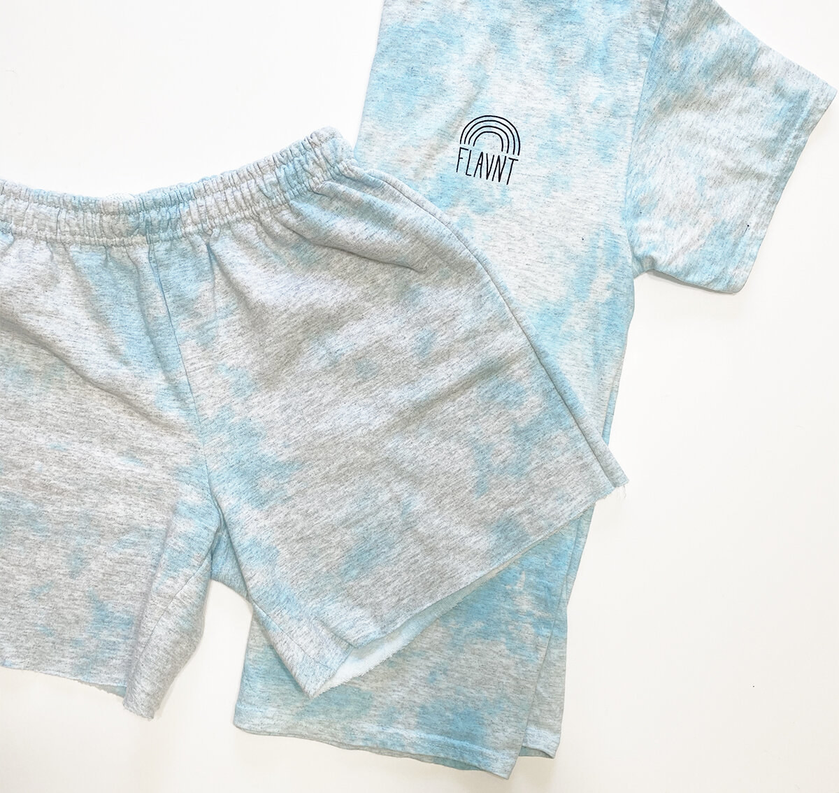 "Sweatpant shorts and a t-shirt both in grey with a blue tie-dye effect on them and the t-shirt has a small logo on the left side with a rainbow shape and the word ""Flavnt"" on it"