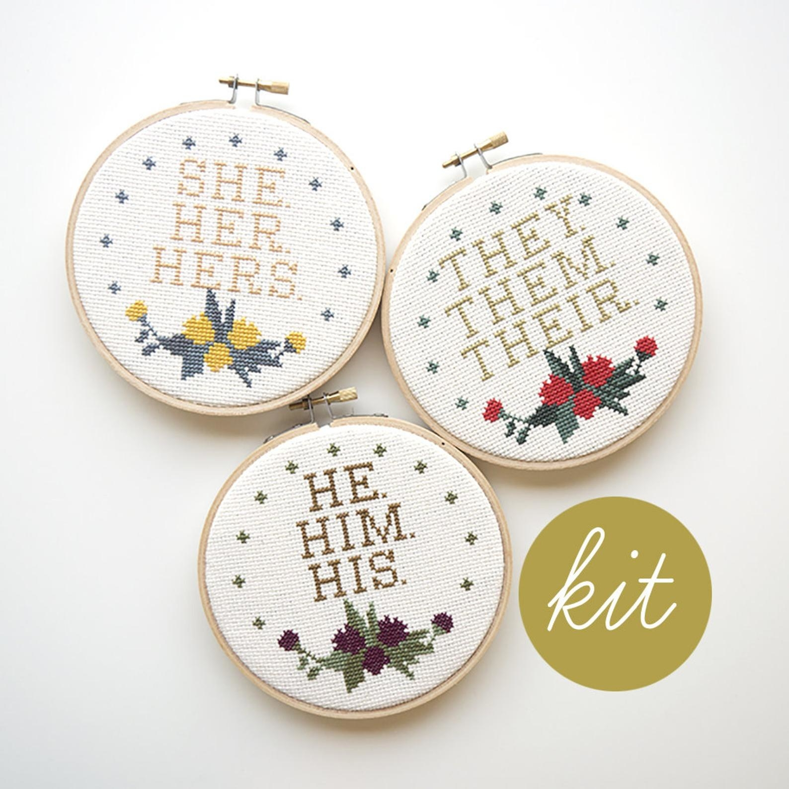 "Three cross stitch loops, all with small floral design at the bottom and the one on the top left has the words ""Sher, Her, Hers"" the top right has the words ""They, Them, Their"", and the one in the middle bottom has the words ""He, Him, His"""