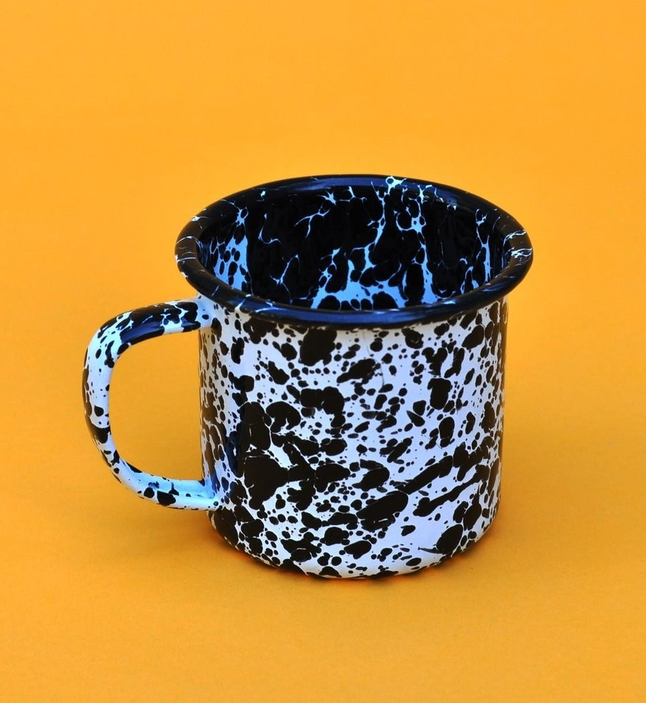 The mug with a lip on the top and black and white speckles