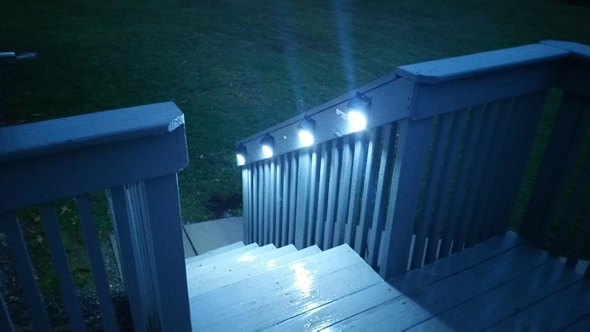 The lights mounted to the side of porch steps and illuminating the stairs