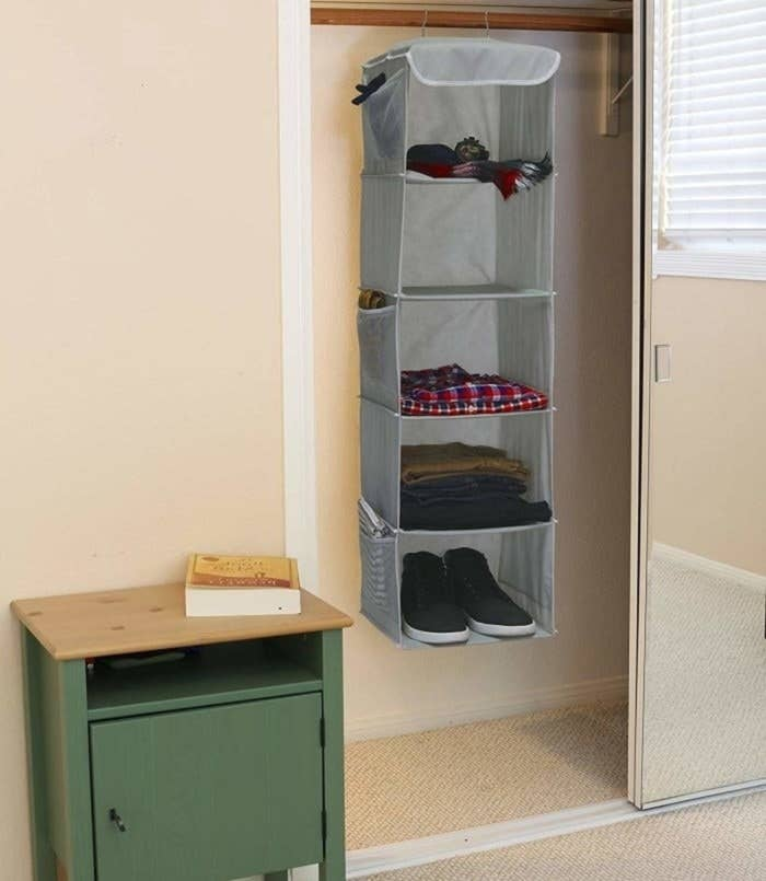 Five-tier hanging shelf with three mesh pockets on the side hanging in a closet in a bedroom