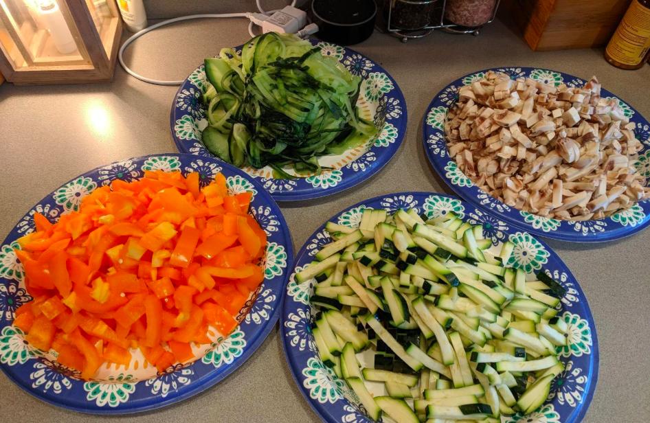Various plates of chopped veggies