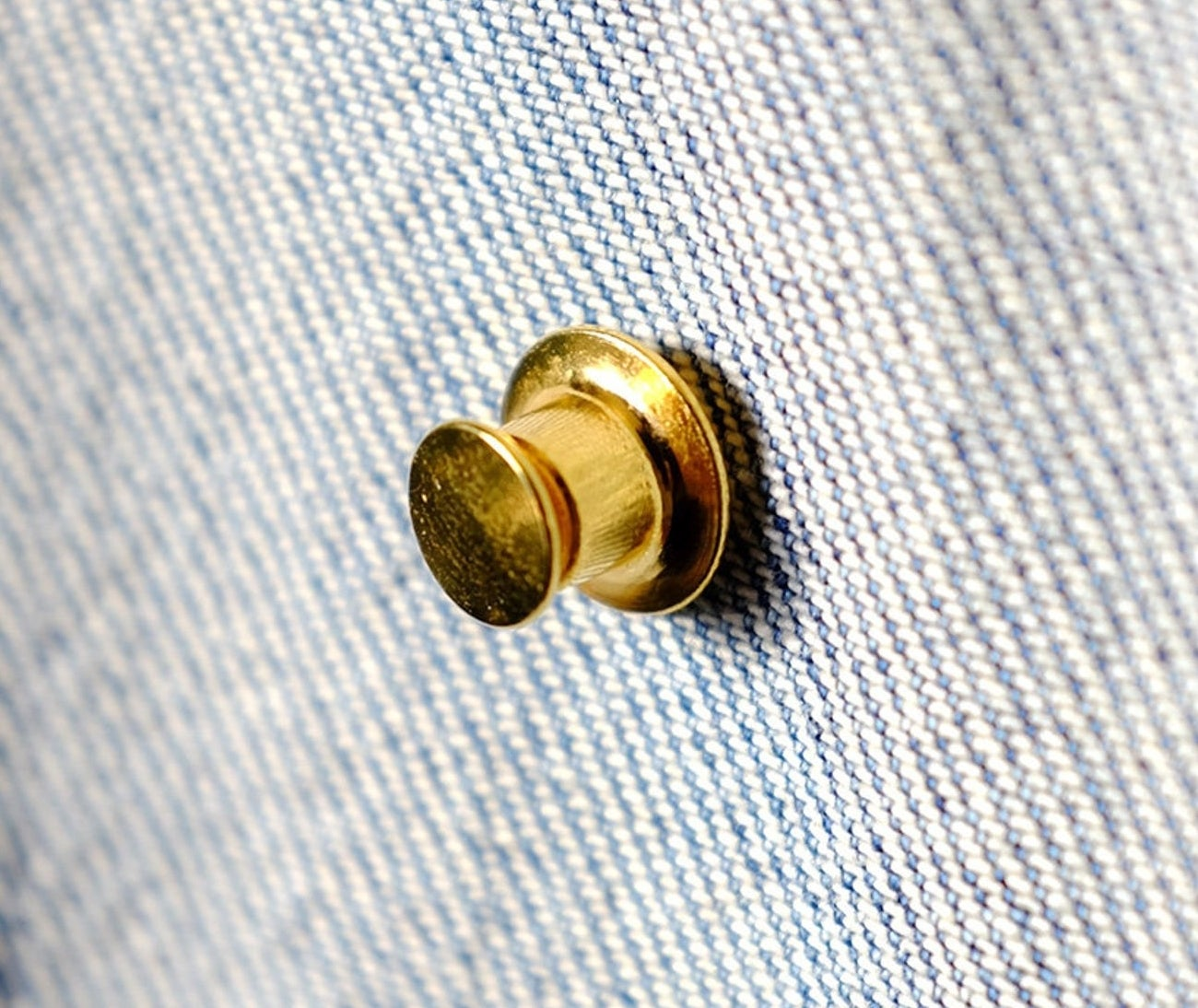 A gold pin backing on the inside of a denim jacket