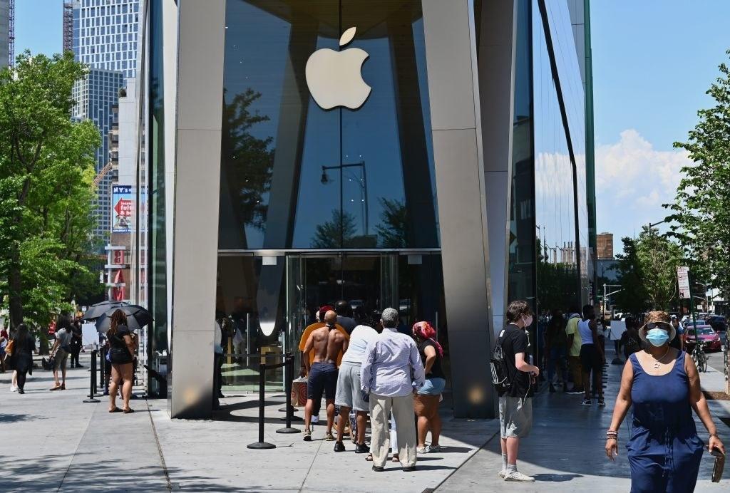 People wait in line outside an Apple store