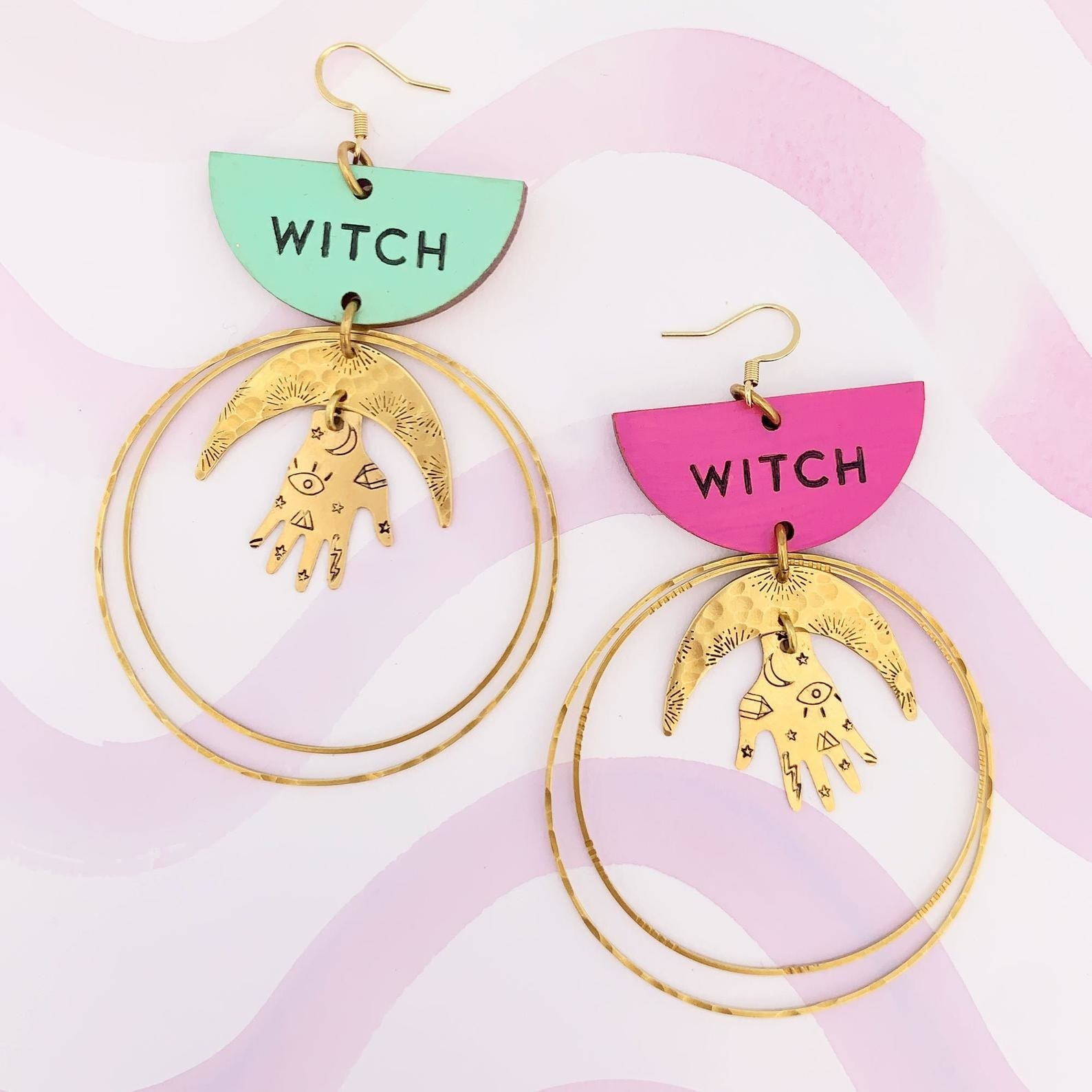 "One mint and one purple earring with a half circle that says ""Witch"" on it and then two gold circles and a half moon and hand with illustrations on it in the middle"