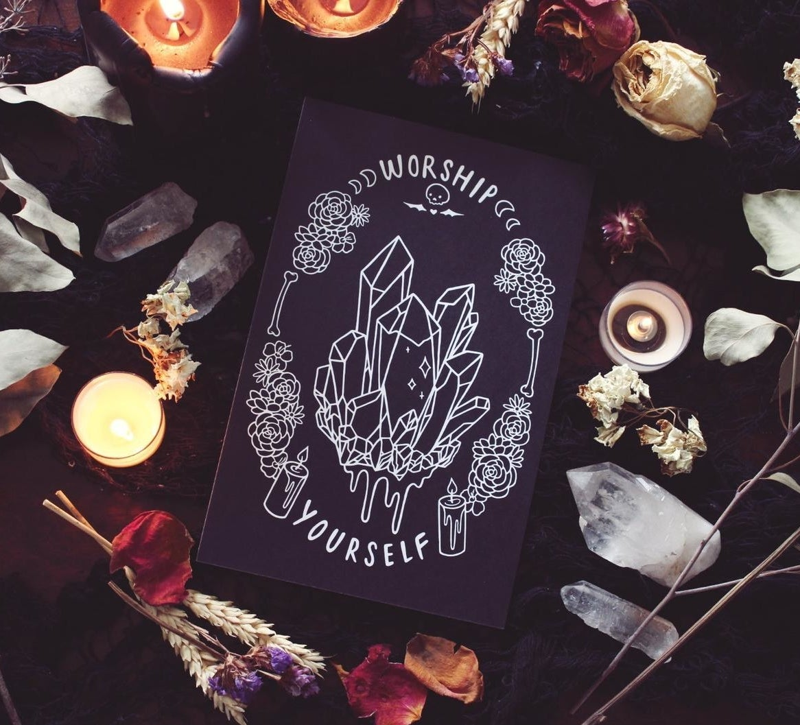 "An art print with illustration in white of crystals in the middle and flowers, candles, bones, and moons in a circle around it with the words ""Worship Yourself"" at the top and bottom"