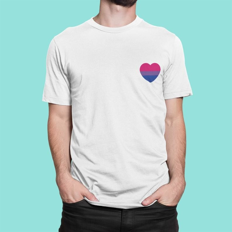 Model wearing white t-shirt with a pink, purple, and blue-striped heart on the top left side