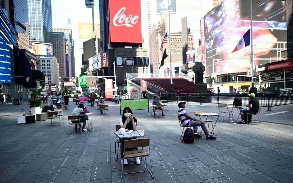 People sit at tables in Times Square