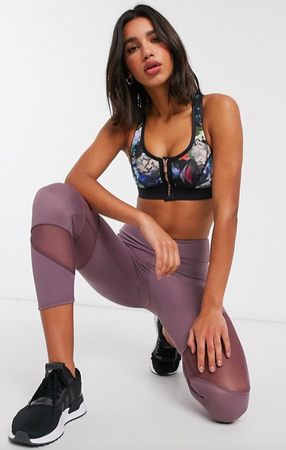Asos model wears a zip-front sports bra with an abstract print