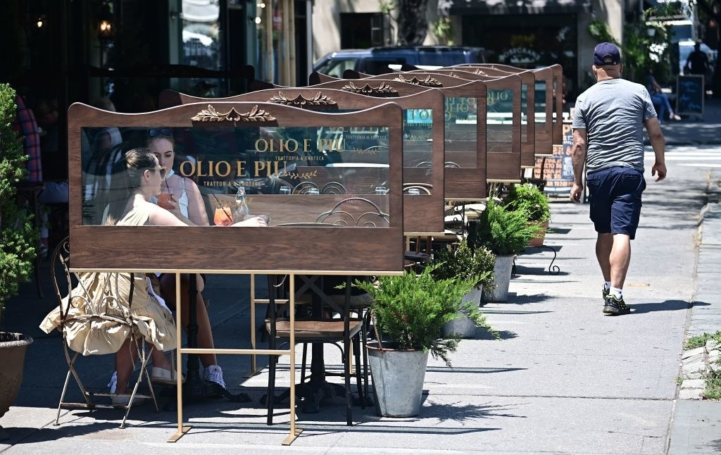 Guests sit outside a restaurant, which has clear panels installed between tables