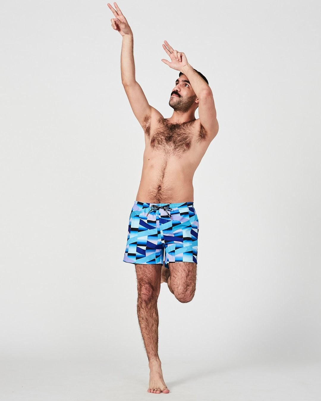 Model wearing the swim shorts with different shades of blue and white geometric rectangle print