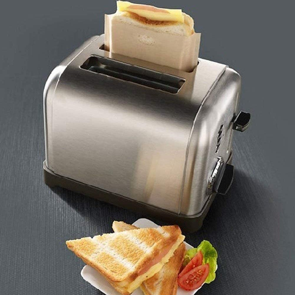 The toaster bag in a toaster with a sandwich inside it.