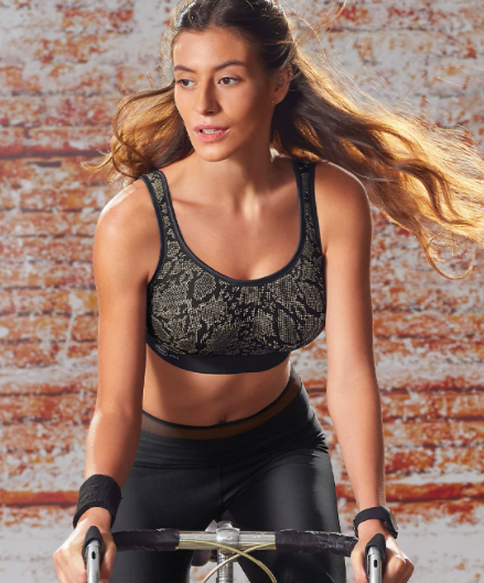 Model wears a snakeskin-print high-impact, wire-free sports bra while cycling