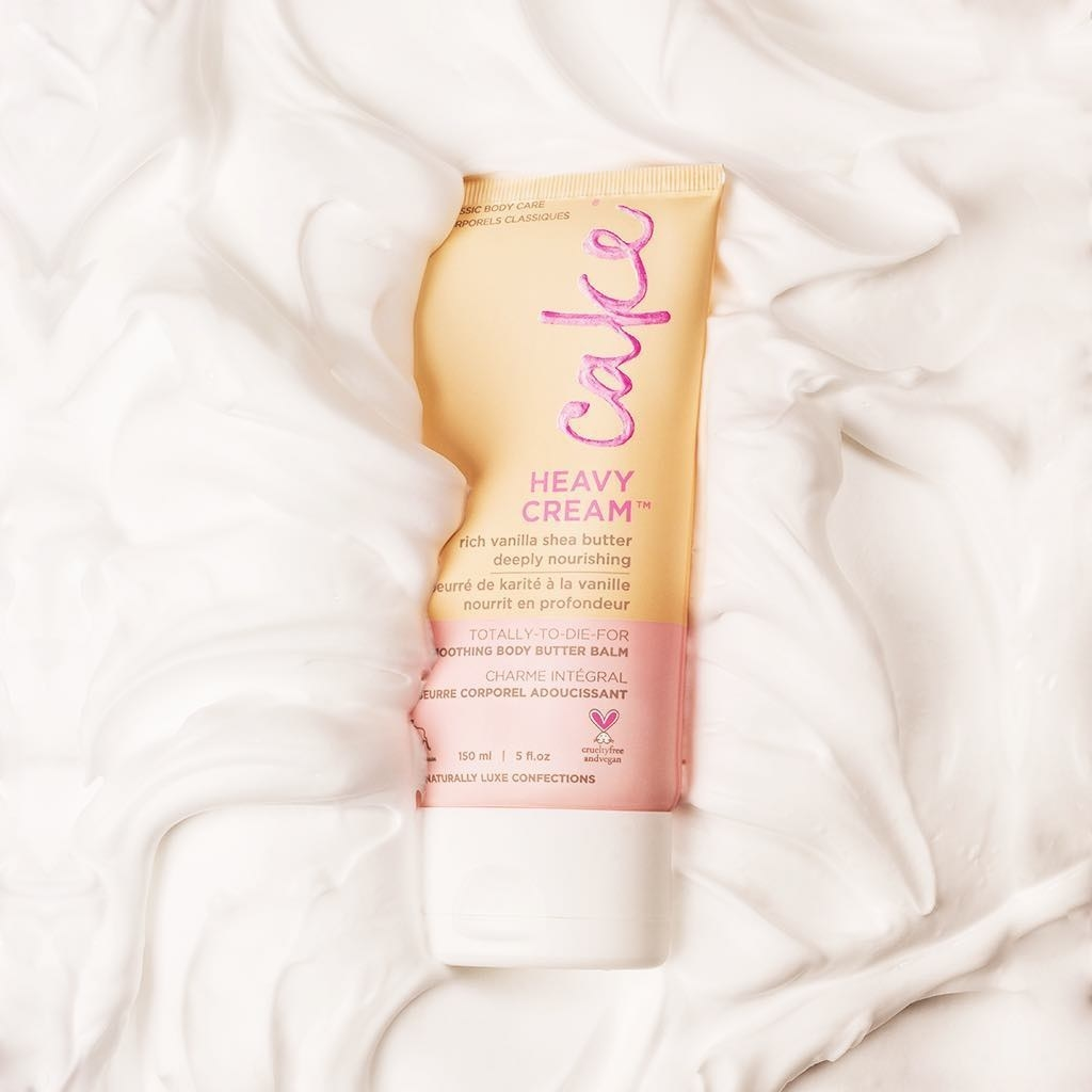 A tube of hand cream lying in a pool of tub of cream