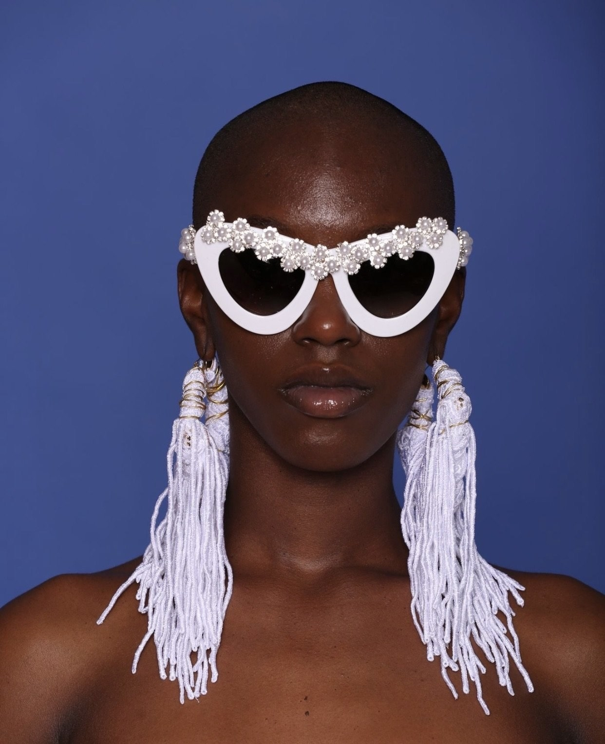 Model wearing the sunglasses in white with small pearl flowers encrusted across the top and on the arms