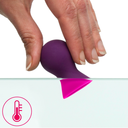 person putting nipple sucker into water showing how it changes from purple to pink when it gets hotter