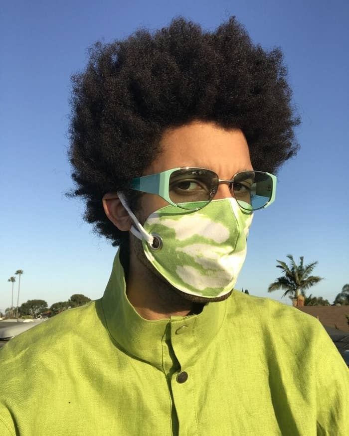 Model wearing the neon green and white cloud-patterned face mask