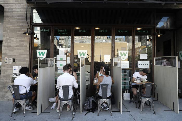 Diners eat their meals separated by dividers in an outdoor restaurant seating area