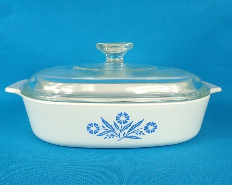 A white casserole dish with blue daisies drawn on it