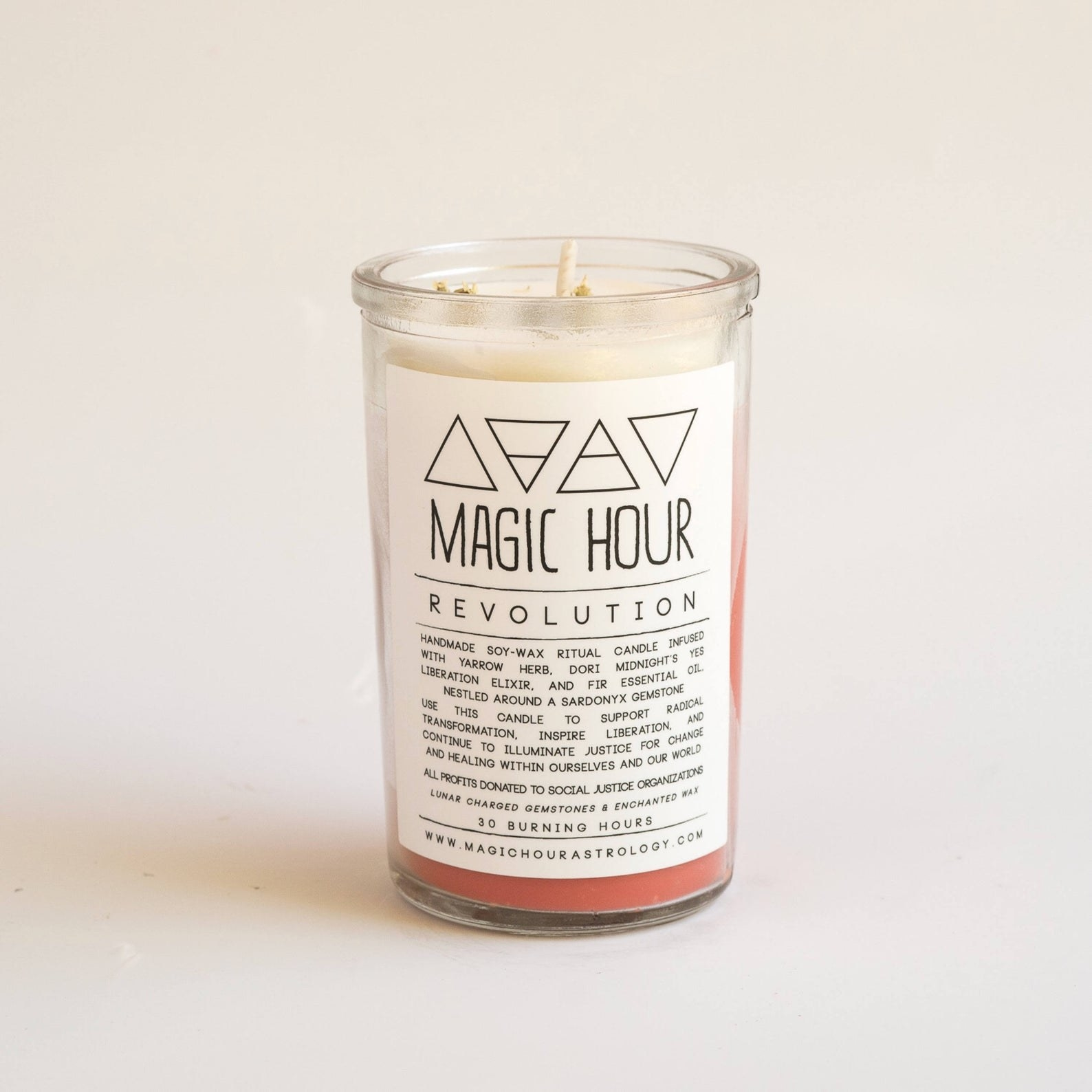 "The candle in a clear glass with ombre peach wax inside and a white label that says ""Magic Hour Revolution"" and then all the ingredients and information below it"