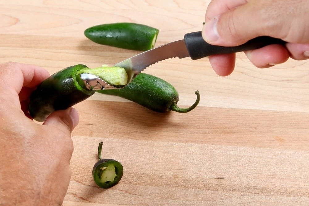 A person using the jalapeno pepper corer.