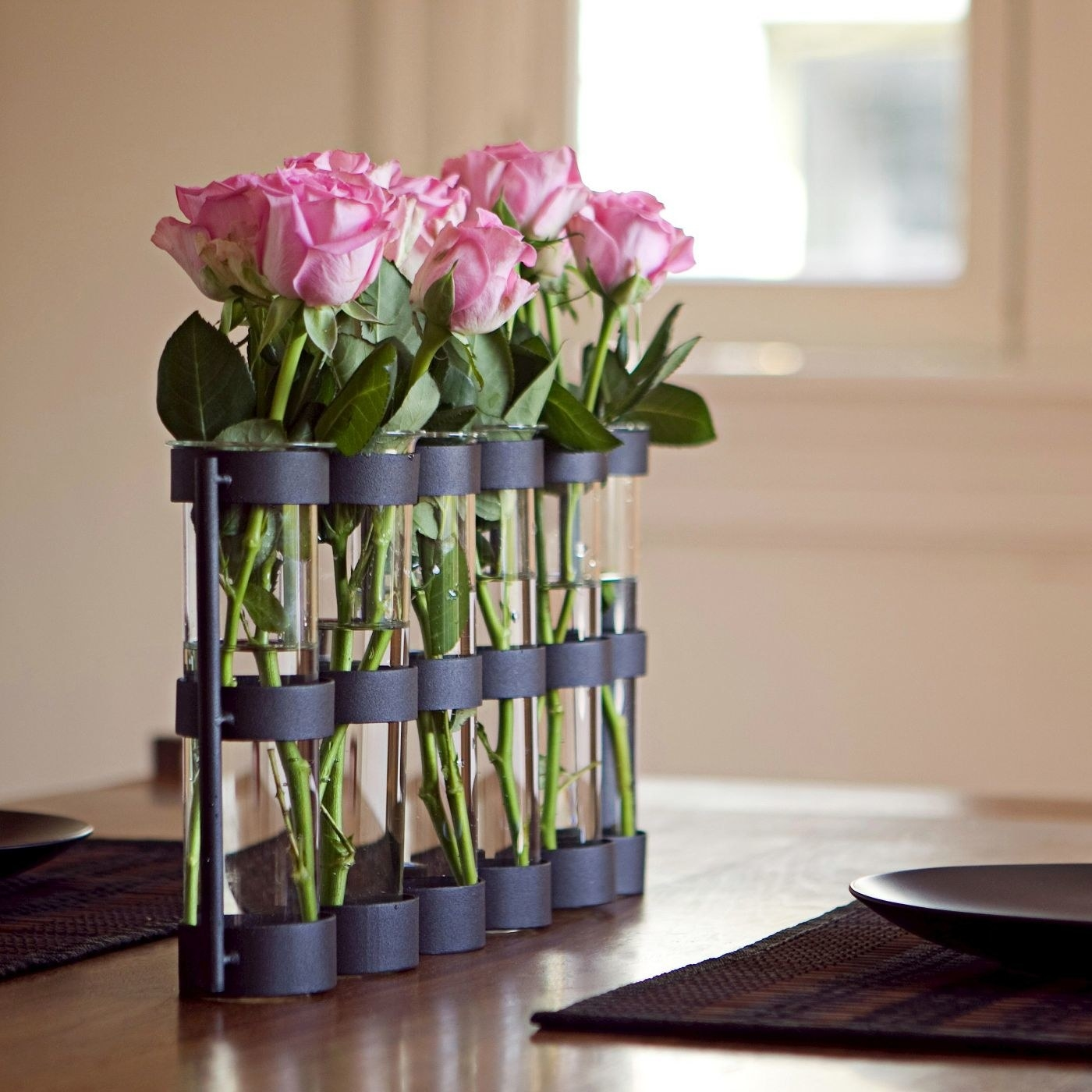 six connected vases with black bases and clear glass