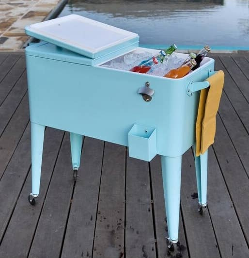 A light blue cooler on caster wheels with the top open revealing ice and cold beverages