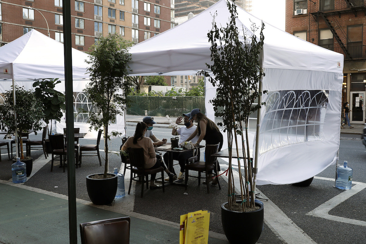 Diners enjoy their meals beneath tents in an outdoor restaurant seating area