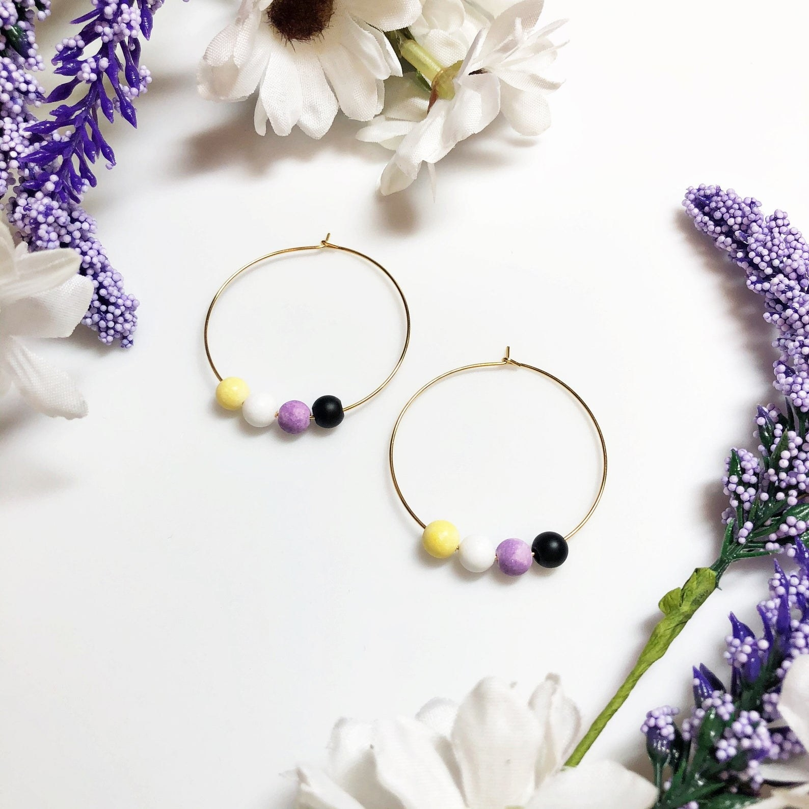 Two thin gold hoops with four small beads on them in yellow, white, purple, and black