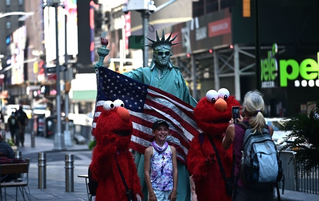 A girl poses with people dressed as the Statue of Liberty and Elmo in Times Square