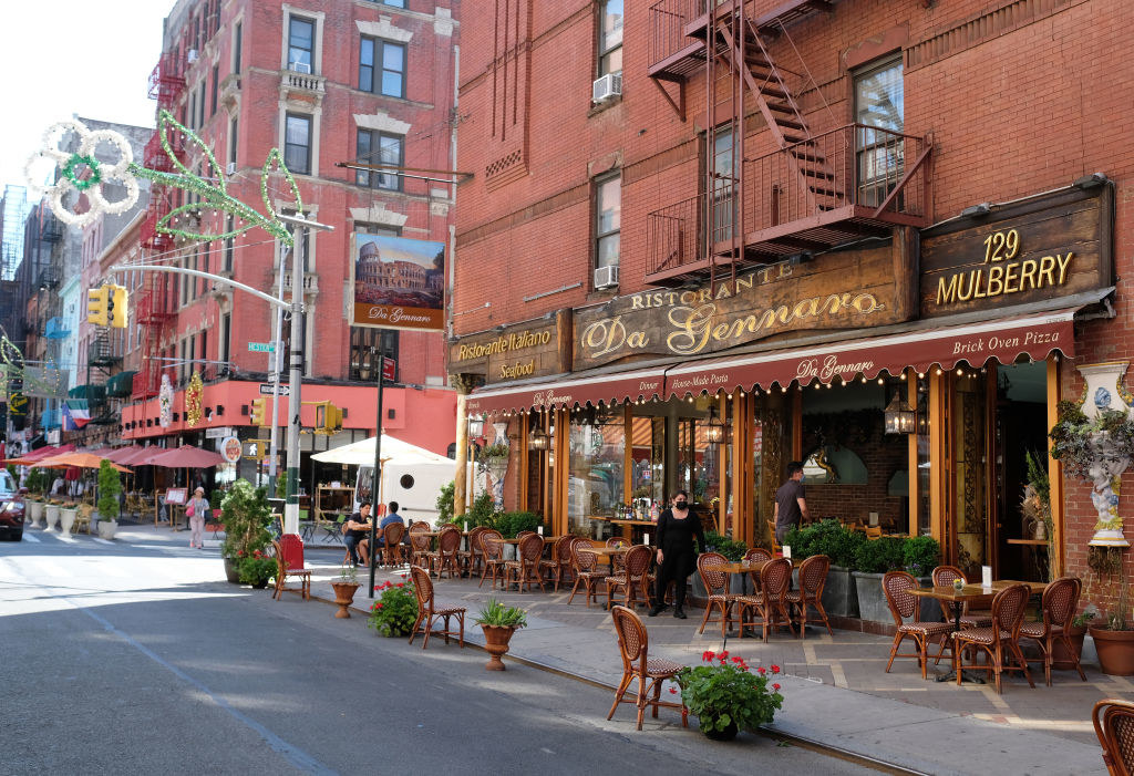 A restaurant in Little Italy serves customers seated at sidewalk tables