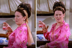 Karen is wearing a gold headband and pink silk shirt, holding a glass of alcohol. She is making a sour face.