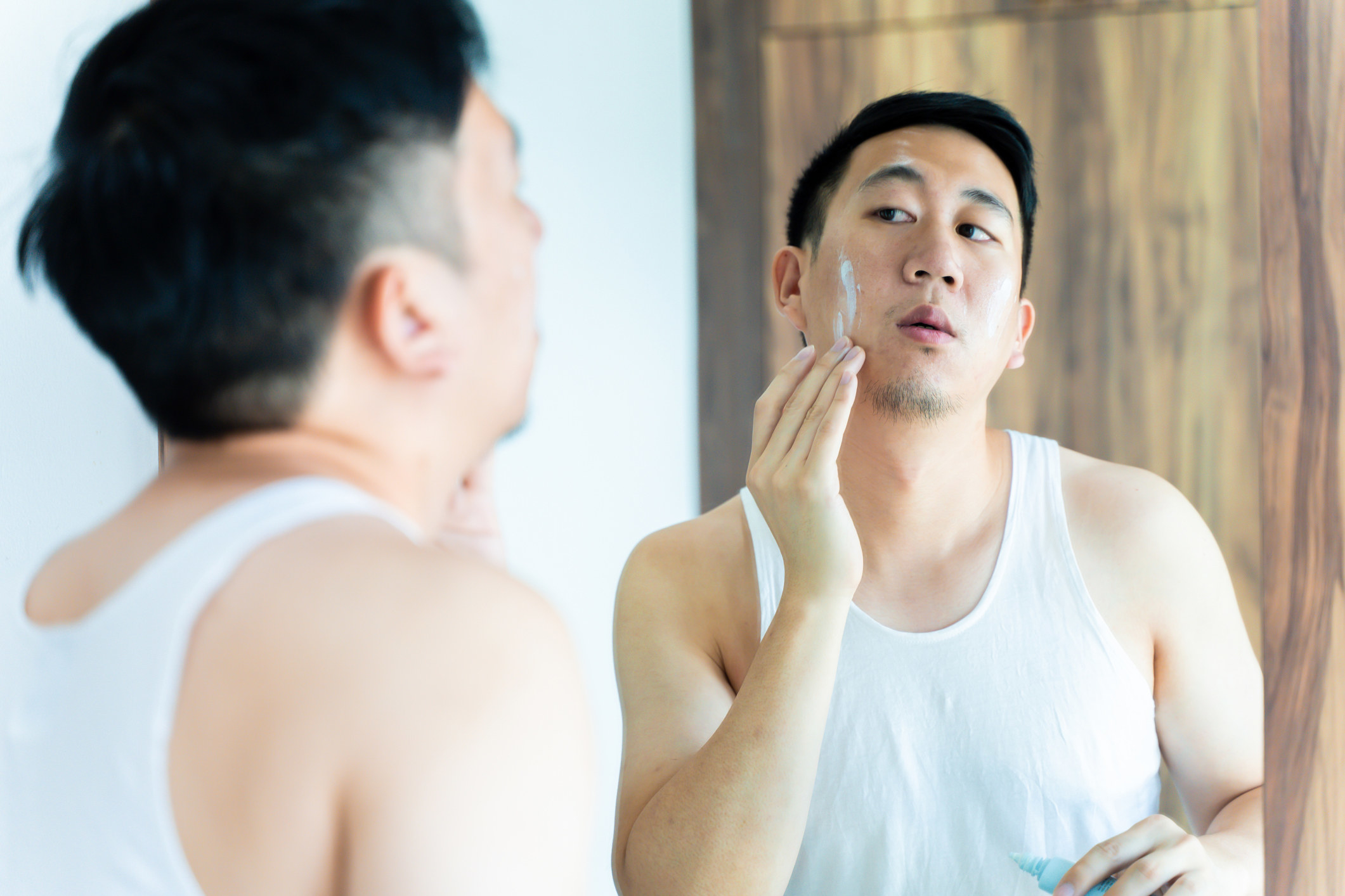 Man moisturizing in mirror
