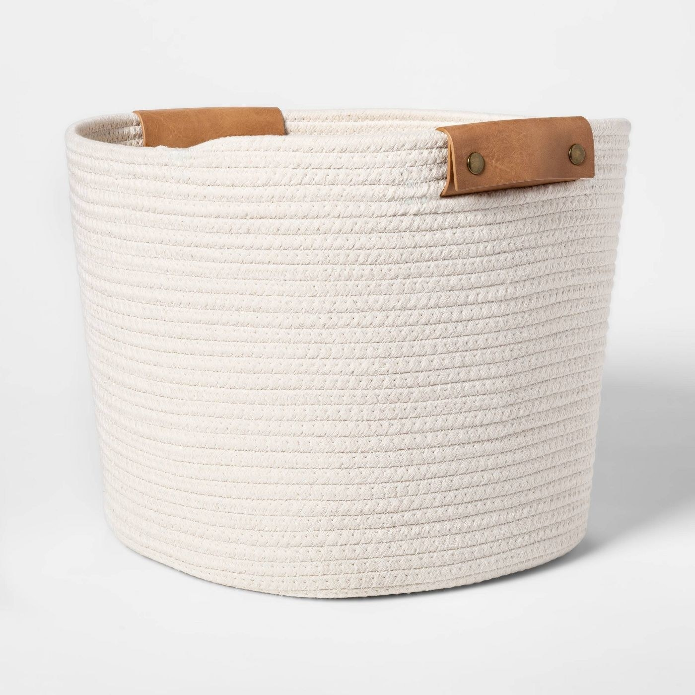 A white woven basket with leather handles