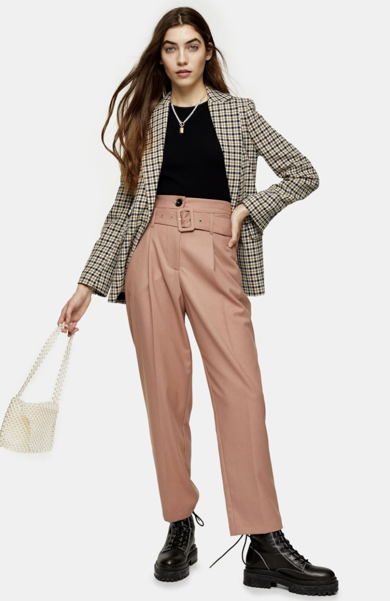 Model wearing the cropped trousers in rose with a belt around the waist