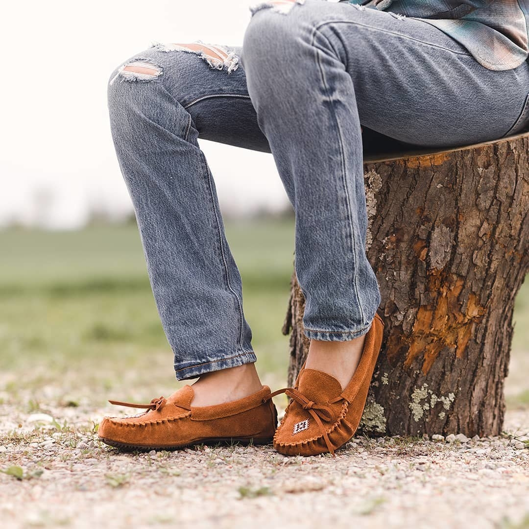 A person sitting on a tree stump wearing jeans and a pair of soft leather moccasins