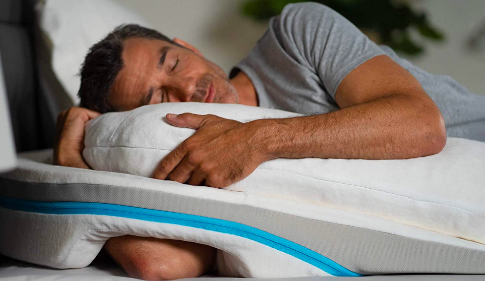 A person sleeping on their side with the pillow. It is lifting their body up and gives their arm a spot to wrap around and hold while the other arm has padded support to prevent the pressure of body weight.