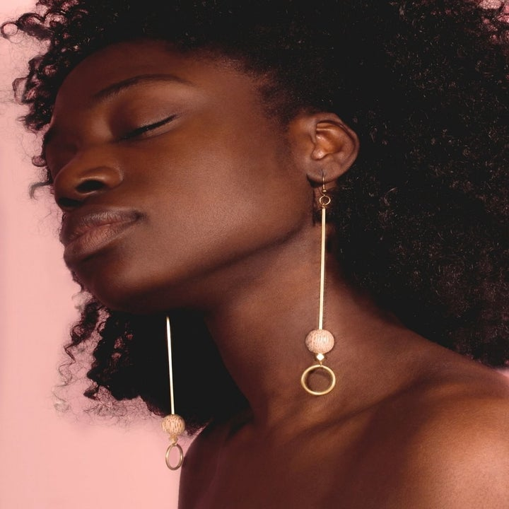 A model wearing the earrings, which almost hit the collarbone