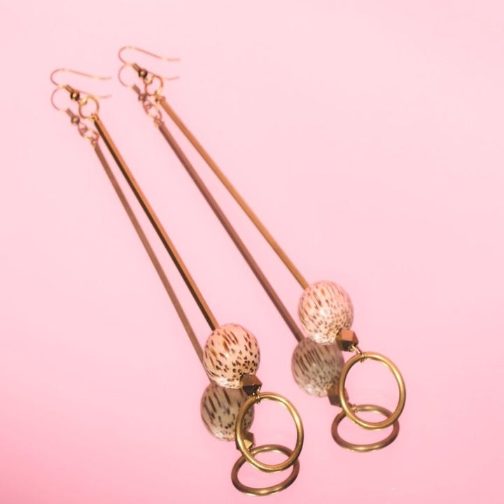 The earrings, which have a long gold chain, a wooden ball, and a gold hoop