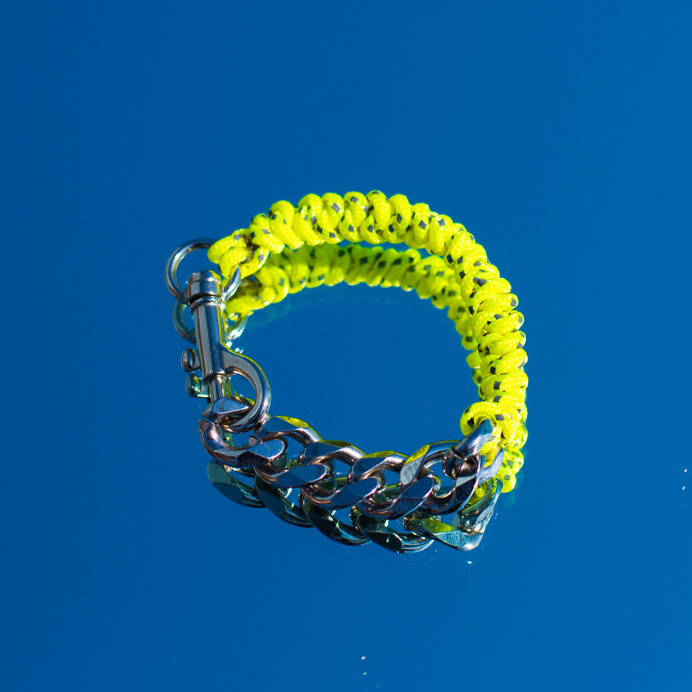 The bright yellow corded chain bracelet laying on top of a mirror